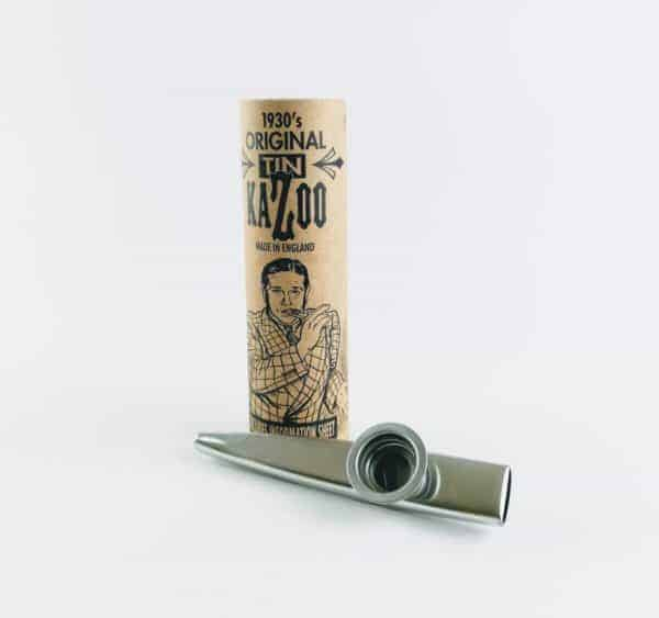 silver kazoo next to packaging tube