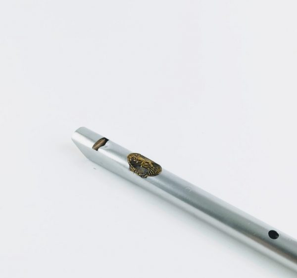 silver clarke original tin whistle laying down on table