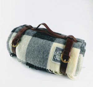 Tolly McRae black and white checked picnic rug rolled up with a leather carry strap