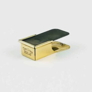 Acme polished brass clicker on white background