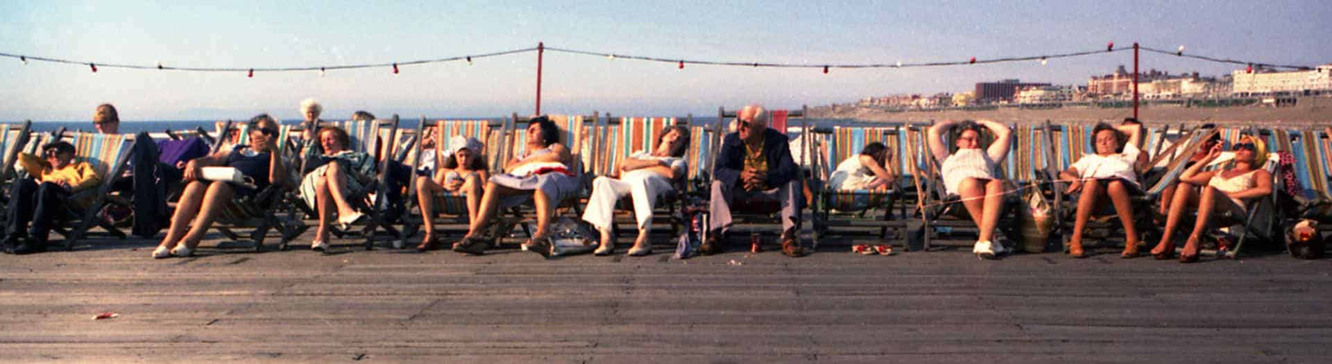 people relaxing on deckchairs on a pier in the 1970's