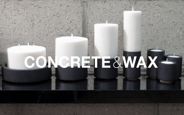 British made concrete and wax black candle holder with white candles