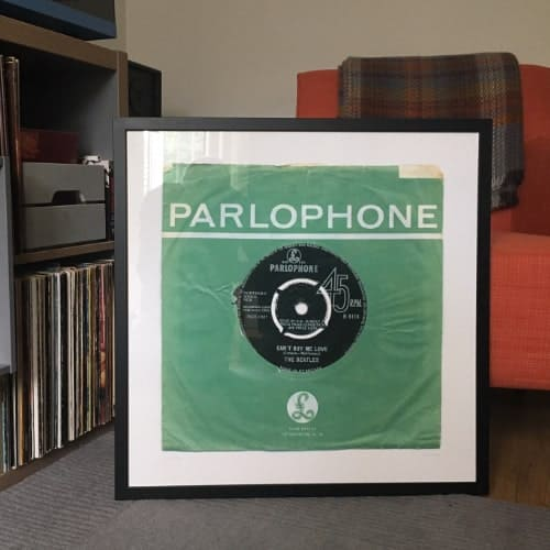 The Beatles Can't Buy Me Love giclee print in black frame sitting on floor