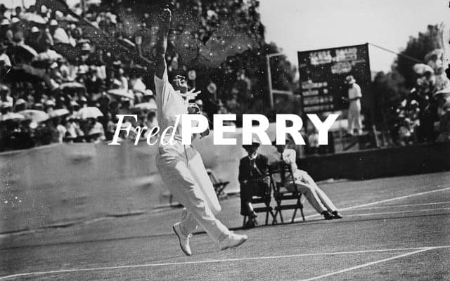 black and white photo of fred perry hitting a tennis ball with fred perry written in white type