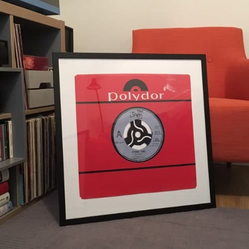 The Jam Strange Town giclee print in black frame sitting on floor
