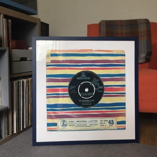 The Beatles We Can Work it out giclee print in black frame sitting on floor